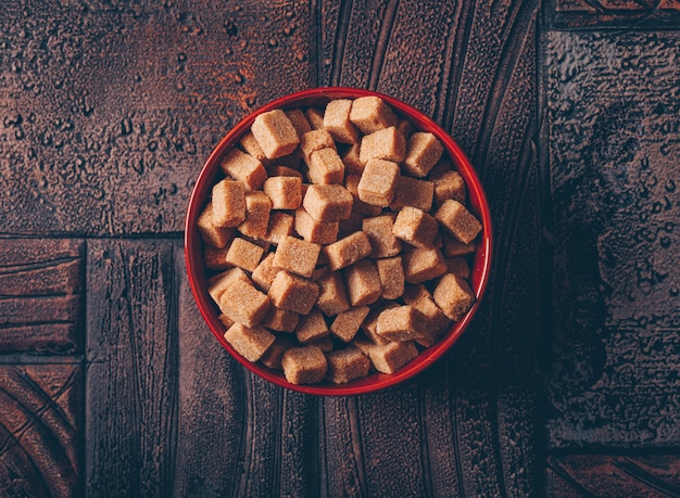 Brązowe kostki cukru w misce na ciemnym drewnianym stole. leżał płasko.