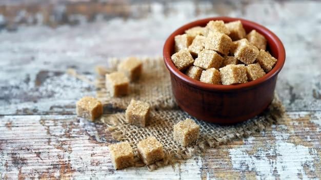 Brązowe kostki cukru w misce.