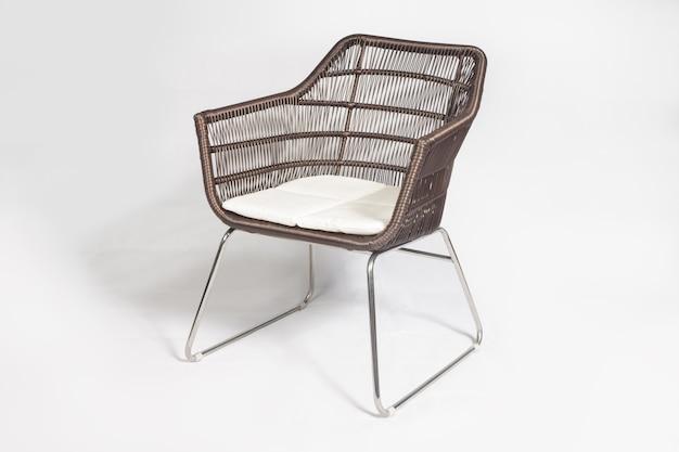 Brązowe nowoczesne krzesło ogrodowe z rattanu z metalowymi nogami na białym tle
