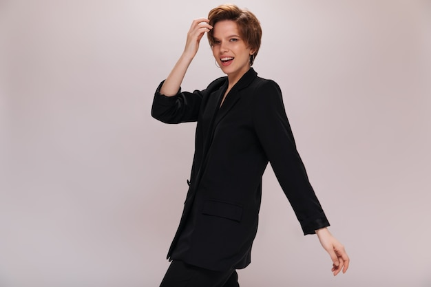 Brązowe oczy pani w ciemnym garniturze porusza się na na białym tle. fajna młoda kobieta w czarnej kurtce i spodniach spacery i uśmiecha się na białym tle