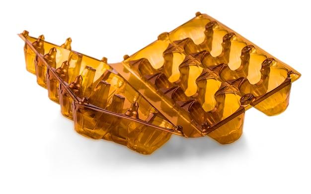 Brązowe otwarte plastikowe pudełko na jajka na białym tle