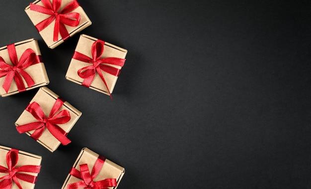 Brązowe pudełka na prezenty z czerwonymi kokardkami na ciemnym tle