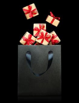 Brązowe pudełka na prezenty z czerwonymi wstążkami wpadające do czarnej torby na prezenty na izolowanym czarnym tle, koncepcja czarnego piątku