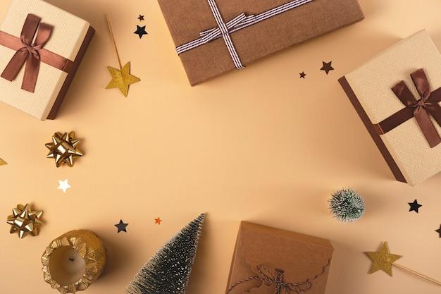 Brązowe pudełka z wstążkami prezenty świąteczne na neutralnym tle z gwiazdami i gałązkami widok z góry płasko leżał kopia przestrzeń