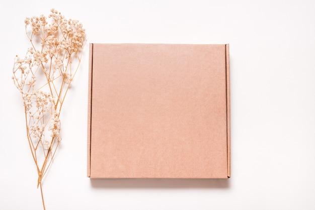 Brązowe pudełko kartonowe ozdobione suszoną trawą