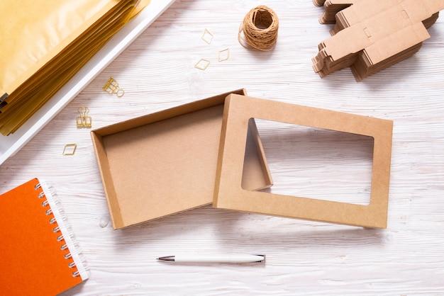 Brązowe pudełko kartonowe z przezroczystą pokrywą na drewnianym stole