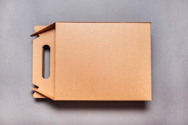 Brązowe pudełko kartonowe z rączką