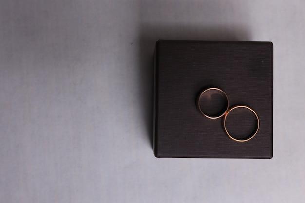 Brązowe pudełko na obrączki ślubne na białym tle