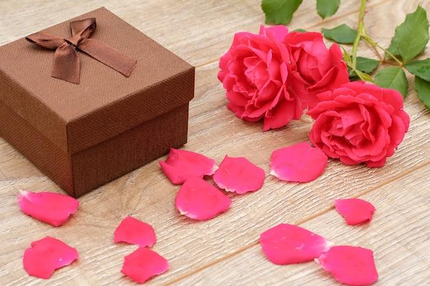 Brązowe pudełko, płatki róż i piękne róże na drewnianym tle. koncepcja dawania prezentu na święta. widok z góry.