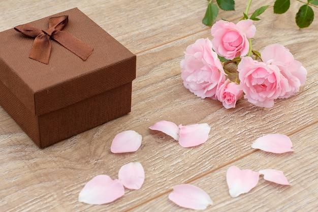 Brązowe pudełko, płatki róż i piękne różowe róże na drewnianym tle. koncepcja dawania prezentu na święta. widok z góry.