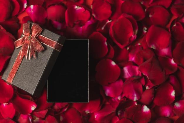 Brązowe pudełko upominkowe umieszczone na czerwonych płatkach róży widok z góry, motyw walentynkowy