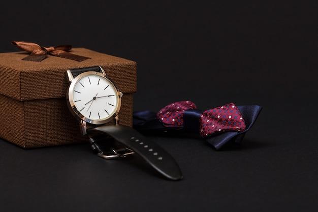 Brązowe pudełko upominkowe, zegarek z czarnym skórzanym paskiem i muszką na czarnym tle. akcesoria dla mężczyzn.