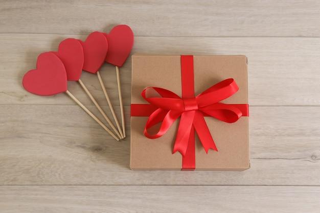 Brązowe pudełko z czerwoną wstążką i sercami.