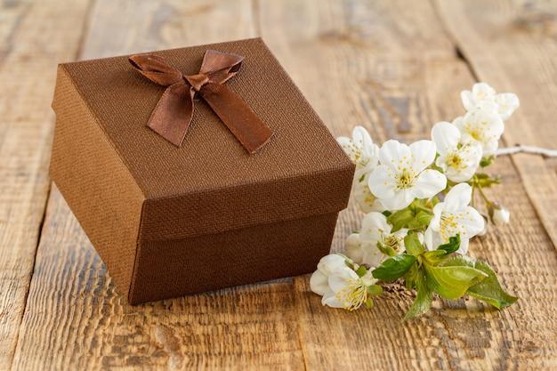 Brązowe pudełko z gałązką pięknych kwiatów jaśminu na drewnianych deskach. koncepcja dawania prezentu na święta.
