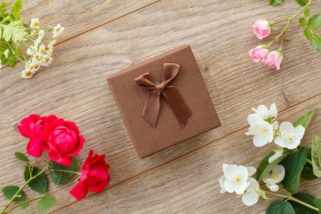 Brązowe pudełko z pięknymi kwiatami róż, jaśminu i rumianku na drewnianym tle. koncepcja dawania prezentu na święta. widok z góry.
