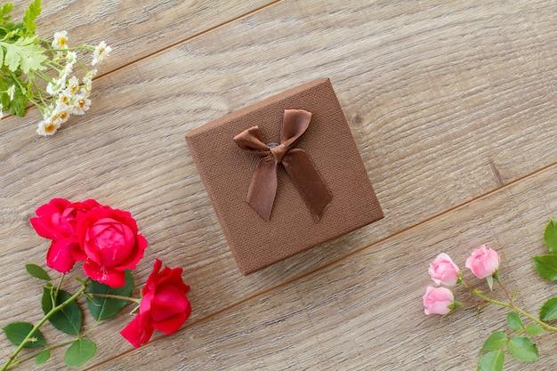 Brązowe pudełko z pięknymi różami i kwiatami rumianku na drewnianym tle. koncepcja dawania prezentu na święta. widok z góry.