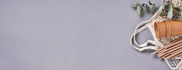 Brązowe rurki do picia słomki z papieru i mąki kukurydzianej, siatkowa torba marketowa i puste papierowe kubki po kawie na modnym szarym tle. koncepcja bez odpadów i plastiku. widok z góry.