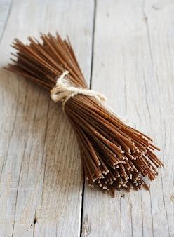 Brązowe spaghetti żytnie na starym drewnianym stole
