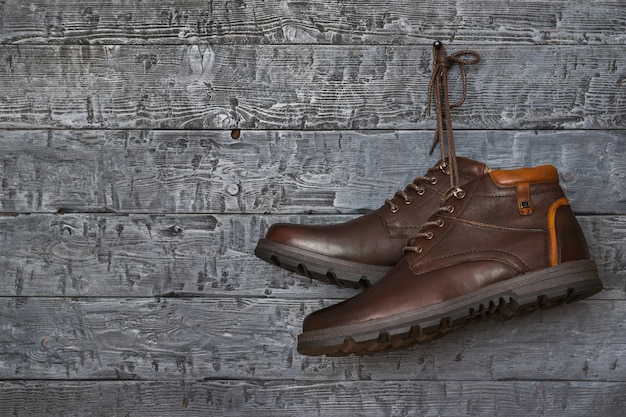 Brązowe stylowe męskie buty wiszące na gwoździu na ścianie w stylu vintage.