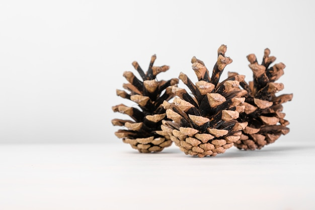 Brązowe szyszki sosnowe samodzielnie na białym stole z miejsca kopiowania. dekoracja świąteczna.