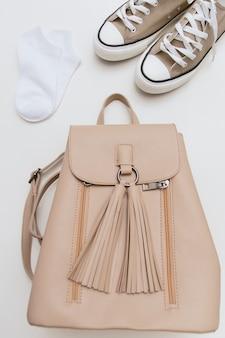 Brązowe trampki, beżowy plecak, białe skarpetki na beżowej ścianie