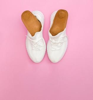 Brązowe wkładki ortopedyczne do butów. białe trampki na różowym tle.