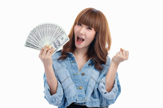 Brązowe włosy azjatycka kobieta trzyma amerykańskie banknoty, które rozłożone w jej dłoni i wznoszą się podekscytowana pięść, studio strzał na białym tle.