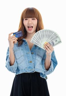 Brązowe włosy azjatycka kobieta trzymająca w dłoni rozłożone amerykańskie banknoty, aw drugiej ręce trzymająca makiety karty kredytowej, studio strzał na białym tle.