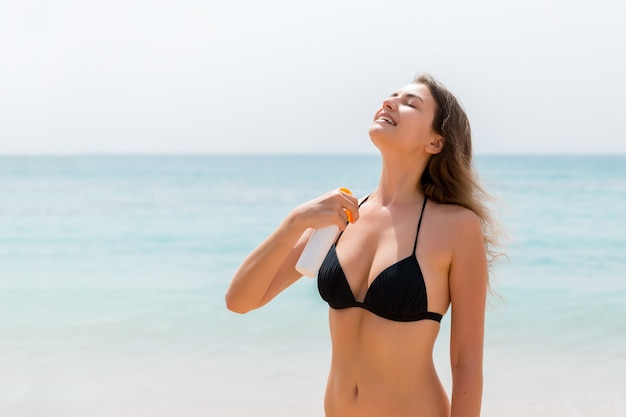 Brązowe włosy kobieta nakłada sunsceen z sprayu na jej ciało na tle morza.