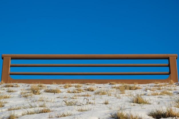 Brązowe żelazne balustrady na tle błękitnego nieba i trawy na śniegu