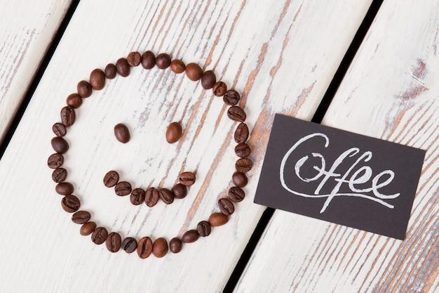 Brązowe ziarna kawy tworzą buźkę. słowo kawy napisane na czarnym papierze. koncepcja pysznej kawy.