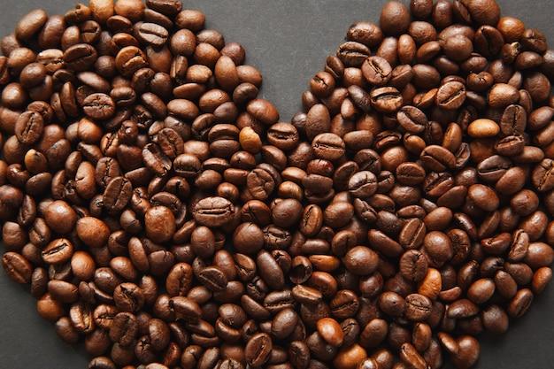 Brązowe ziarna kawy w formie serca na białym tle na czarnym tle tekstury dla projektu, części lub połowy. karta świętego walentego na 14 lutego, koncepcja wakacje.