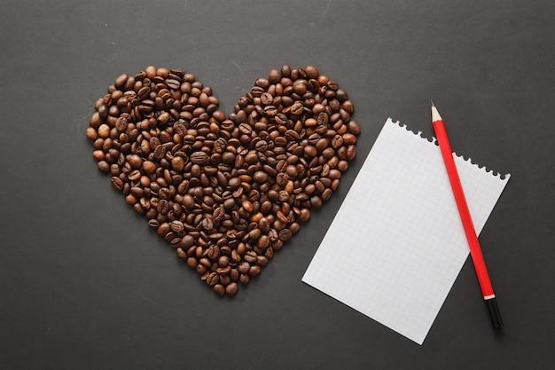 Brązowe ziarna kawy w formie serca na białym tle na czarnym tle tekstury dla projektu. karta świętego walentego na 14 lutego, koncepcja wakacje. notatnik, biały pusty arkusz, czerwony ołówek. miejsce na tekst