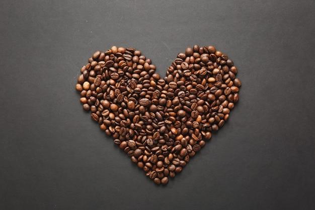 Brązowe ziarna kawy w formie serca na białym tle na czarnym tle tekstury dla projektu. karta świętego walentego na 14 lutego, koncepcja wakacje.