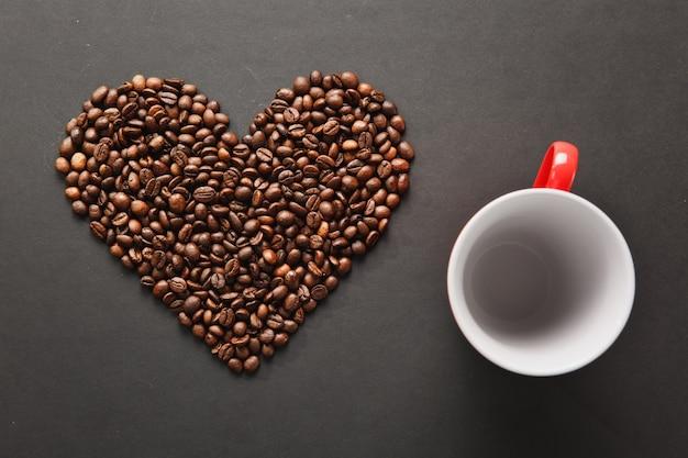 Brązowe ziarna kawy w formie serca z czerwonym filiżanką na herbatę z sercami na białym tle na czarnym tle tekstury dla projektu. karta świętego walentego na 14 lutego, koncepcja wakacje.
