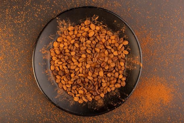 Brązowe ziarna kawy z widokiem z góry na czarnym talerzu na brązowym stole