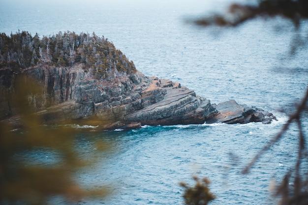 Brązowo-zielona formacja skalna na zbiorniku wodnym w ciągu dnia
