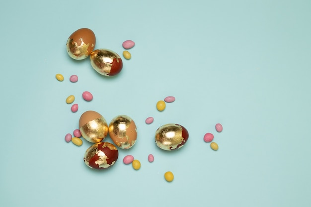 Brązowo złote pisanki i kolorowe cukierki w żelkach na niebieskim tle z copyspace