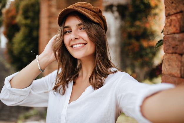 Brązowooka dziewczyna w aksamitnej czapce i białej bluzce robi selfie w przestrzeni ceglanego muru i drzew.