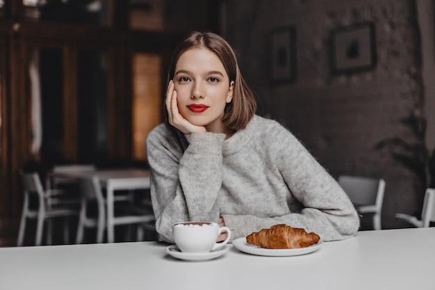 Brązowooka dziewczyna w wełnianym swetrze oparła się na białym stole w kawiarni i patrząc na kamery. zdjęcie kobiety z czerwonymi ustami zamawiającej kawę i rogalika.