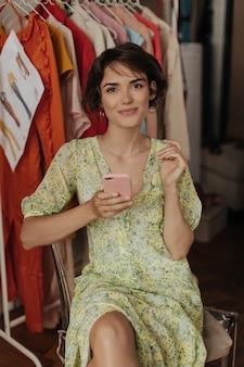 Brązowooka kręcona brunetka w kwiecistej żółtej sukience szczerze się uśmiecha, patrzy z przodu i trzyma telefon w różowej obudowie w garderobie