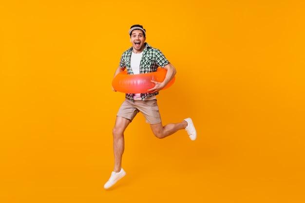 Brązowooki brunet w beżowych szortach i zielonej koszulce skacze z nadmuchiwanym kółkiem na pomarańczowej przestrzeni.