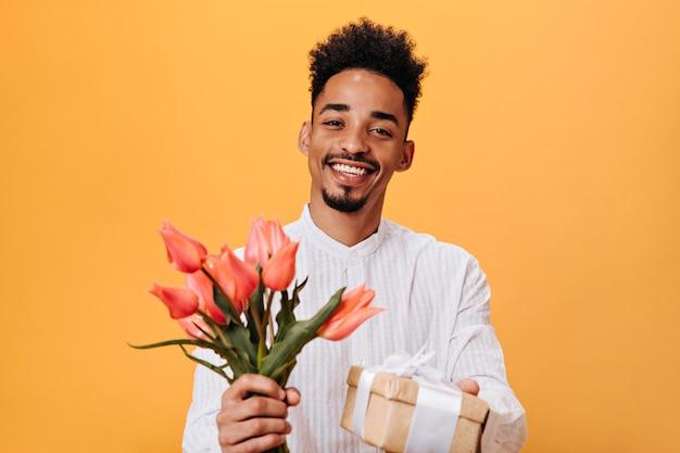 Brązowooki facet w białej koszuli, trzymający różowe tulipany i prezent na pomarańczowej ścianie