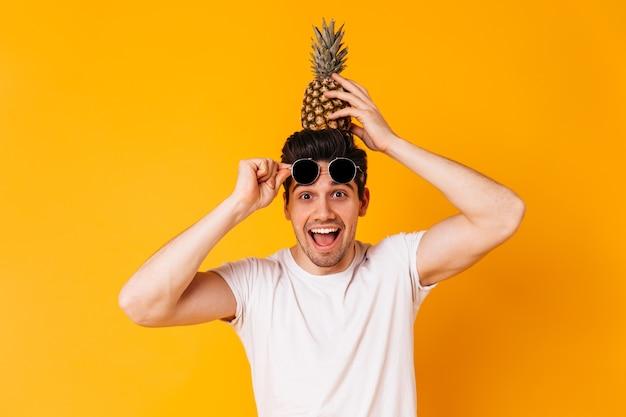Brązowooki niegrzeczny mężczyzna zdejmuje okulary przeciwsłoneczne i trzyma na głowie ananas.
