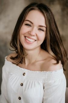 Brązowowłosa dziewczyna w krótkich dżinsowych szortach i białej bluzce na krześle