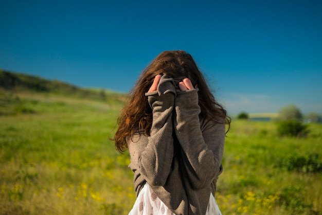 Brązowowłosa dziewczyna zakryła twarz rękami