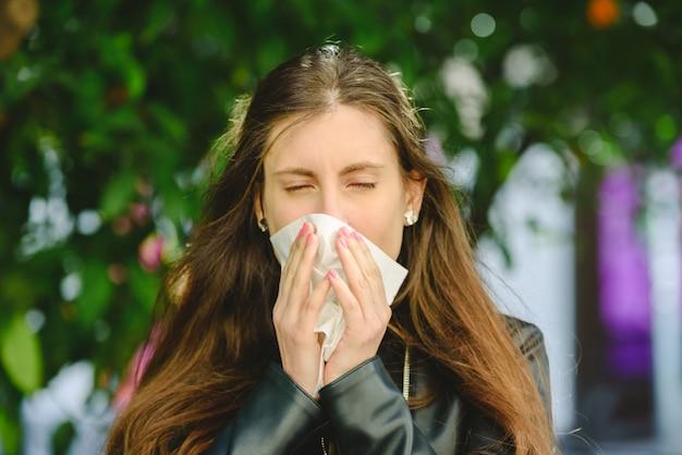 Brązowowłosa kobieta używa chusteczki, aby wydmuchać nos i oczyścić nos z przeziębienia.