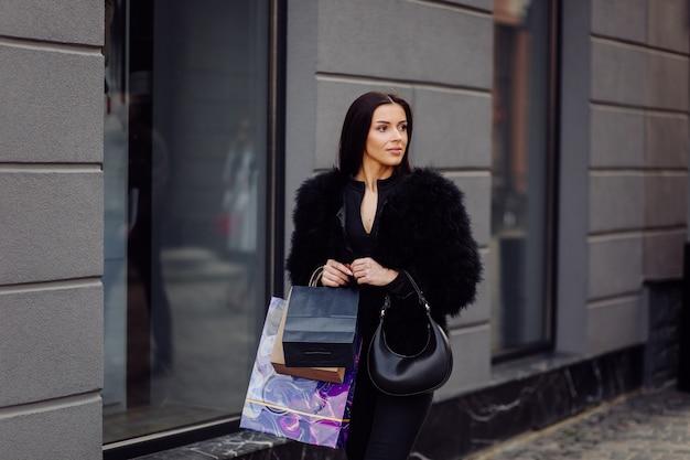 Brązowowłosa kobieta w czarnym stroju trzyma kolorowe, wzorzyste torby na zakupy podczas udanych zakupów. wychodząc na zewnątrz, cieszy się ciepłem dnia