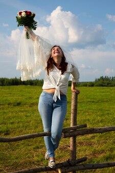 Brązowowłosa kobieta w welonie i dżinsach z bukietem czerwonych i białych róż na tle wiejskiego pola i nieba, bukiet panny młodej, budżetowy nowoczesny ślub w naturze