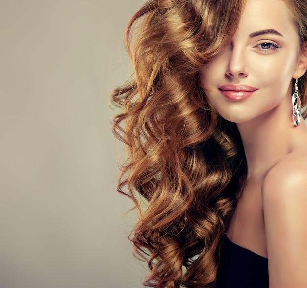 Brązowowłosa kobieta z elegancką obszerną i kędzierzawą fryzurą.